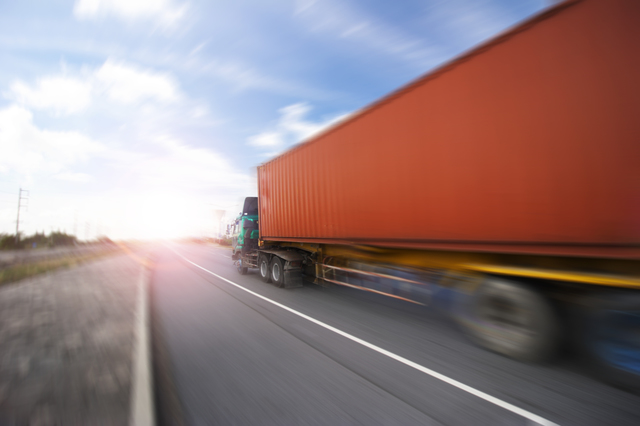 Generic big trucks speeding on the highway at sunset - Transport industry concept , big truck containers